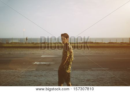 Attractive young white brazilian guy with black hair cross-earring motley shirt and black shorts standing on street and looking into camera summer evening Rio de Janeiro Brazil