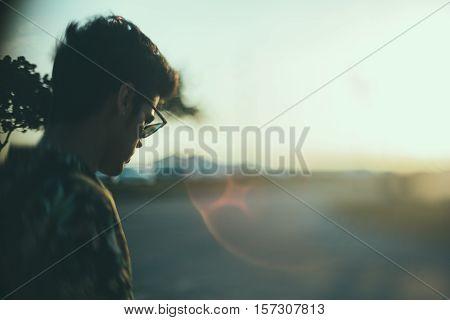 True tilt shift shooting of white brazilian guy in sunglasses and motley shirt near road rear view summer evening in Rio de Janeiro Brazil