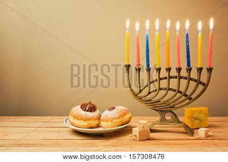Jewish holiday Hanukkah celebration with menorah and sufganiyot on wooden table