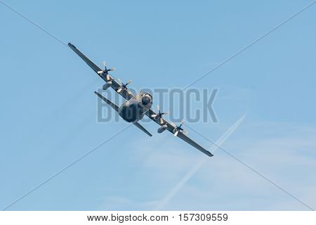 C-130 Hercules cargo plane in flight on blue sky.