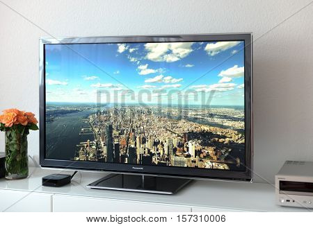 PARIS FRANCE - NOV 21 2015: Apple TV device next to 4k Pansonic Plasma OLED display projecting the typical Apple Screensaver of aerial city