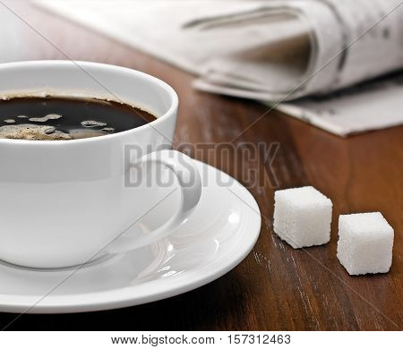 Coffee cup lump sugar (sugar cubes) and newspapers on a wood table studio shot