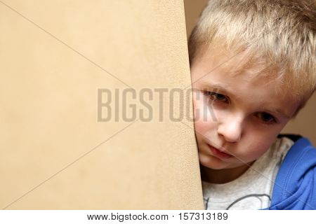 Portrait of a sad child next to wall