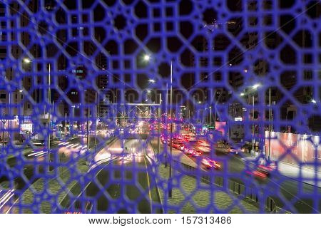 View of a busy road at night from a bridge for pedestrians. A beautiful mosaic on the Pedestrian Bridge in Abu Dhabi. Lights on the road at night. United Arab Emirates Long trail.
