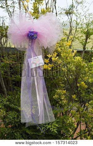 View a pink ribbon as a decoration for a baptism