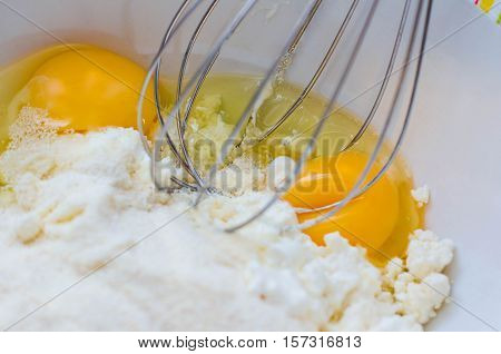 Mix ingredients for dough cheese pie. Semolina, two eggs, sour cream, flour, salt and sugar