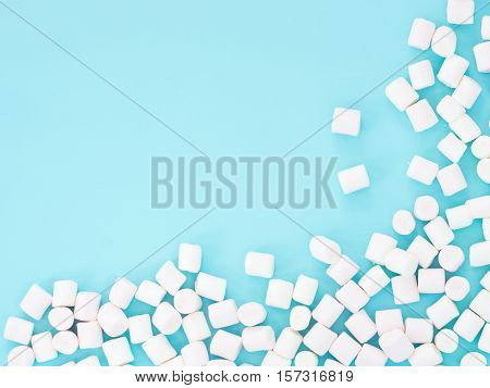 Marshmallows on blue background with copyspace. Flat lay or top view. Background or texture of colorful mini marshmallows.