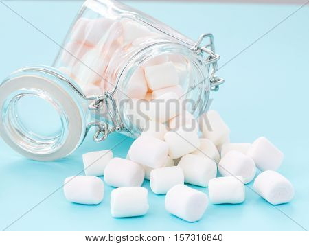 Marshmallow in glass jar on blue background. Close up