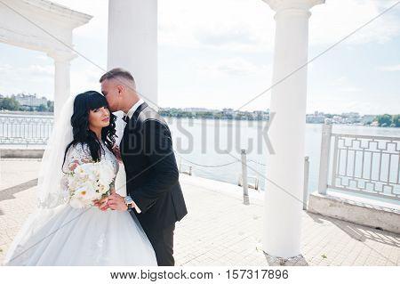 Superb Wedding Couple Under White Columns Monument Background Lake On Sunny Wedding Day Against Blue