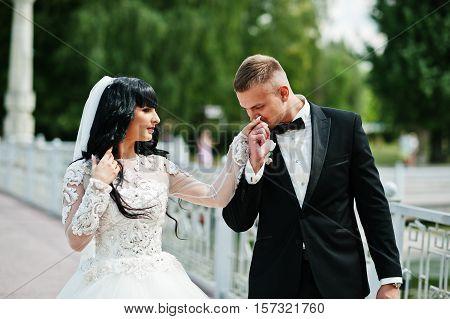 Amazing Wedding Couple Walking On Bridge. Groom Kiss Hand Of Bride.