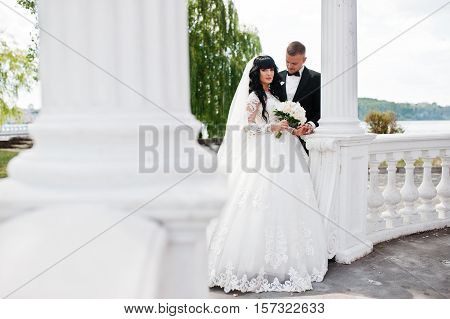 Magnificent Wedding Couple Near White Columns Of Arch Of Love.