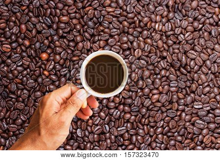 Business man holding a cup of coffee with blur coffee beans background. copy space