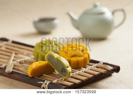 Two mooncakes, half cut showing inside with Chinese tea background