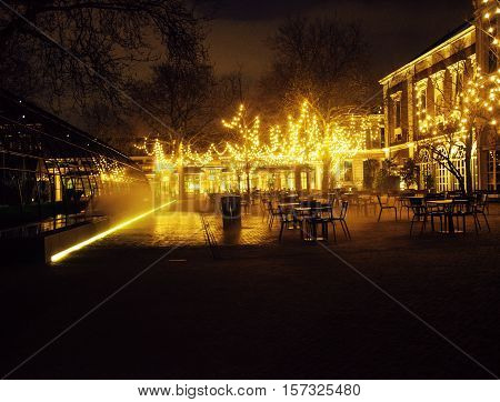 empty night restaurant, lot of tables and chairs with noone, magic fairy lights on trees like christmas view