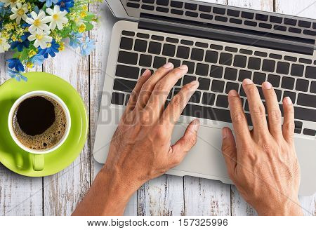 Business man hand working on laptop computer on wooden desk in office. Business concept