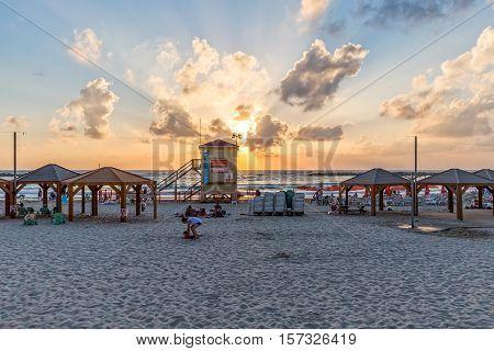 TEL AVIV, ISRAEL - JUNE 19, 2015: People enjoying beautiful sunset on the beach.