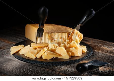 Cheese parmesan with a set of knives on a black round slate board in style a rustic