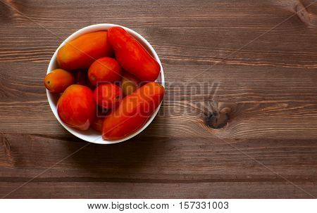 Tomatoes in a plate on a wooden background.