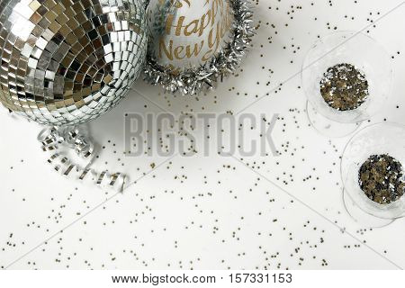 New Years Eve background. Silver disco ball, party hat, confetti, ribbon and two glasses filled with confetti.