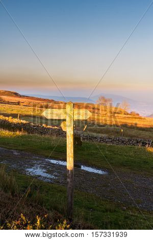 Finger sign post catching the last ray of sun at sunset. To Pwll Du Gilwern Hill and Tyla. Blorenge Abergavenny Wales United Kingdom.