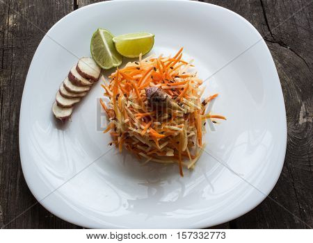 Jerusalem artichoke and carrot salad. olive oil, and flax seeds. white plate. vegetarian dish