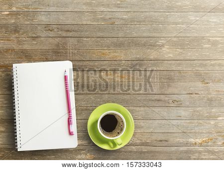 Blank paper notebook with pen and cup of coffee on wooden table.View from above.Office supplies and gadgets on desk table.Working desk table concept.Writing notes.