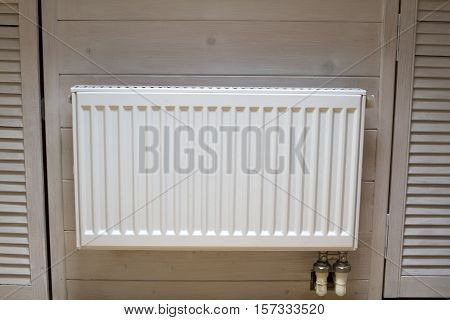 radiator battery white wooden walls at home