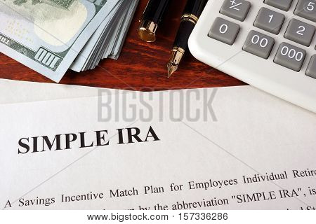 Papers with simple ira and book on a table.