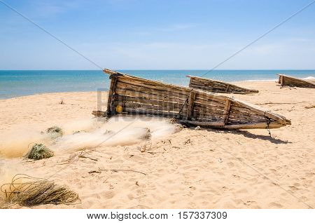 Crude wooden fisher boats lying on yellow beach near Lobito, Angola. These boats have been used traditionally by the locals but nowadays plastic nets prevail.