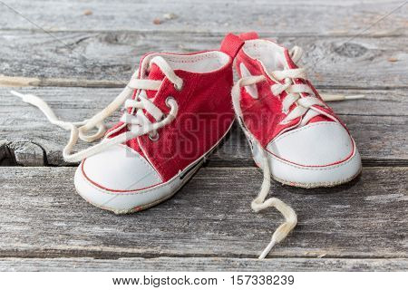 red and white baby sneakers on a wood background