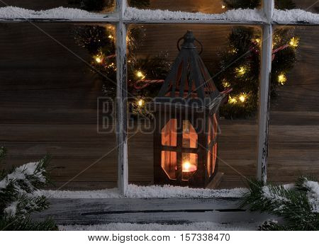 View of a glowing lantern and Christmas wreath through a snow covered window with fir branches.