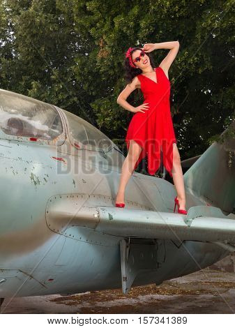 Sexy pin-up model in flashy red dress posing on a wing of a WW2 airplane