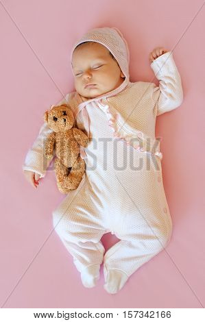 baby girl in white hat and pink pajamas hugging teddy bear sleeps in his bloodstream on a pink blanket