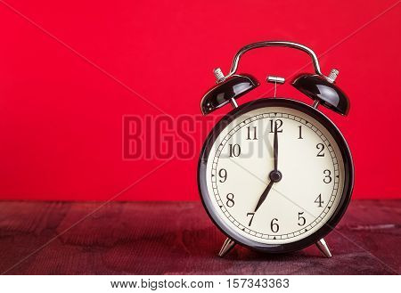 It's Seven O'clock Already, Time To Wake Up For Love, Vintage Old Black Metallic Alarm Clock On Red