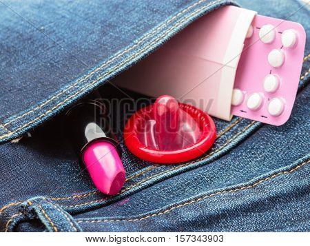 Healthcare medicine contraception and birth control. Closeup oral contraceptive pills condom and pink lipstick in denim pocket.