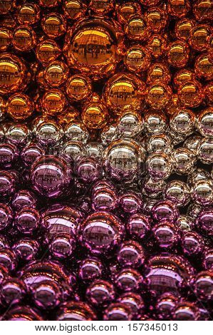 Filled frame composition with colorful Christmas balls of orange silver and purple color. Selective focus. Vertical