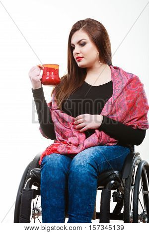 Disability drink relax leisure concept. Cheerful crippled lady on wheelchair. Smiling disabled girl holding red cup drinking beverage.