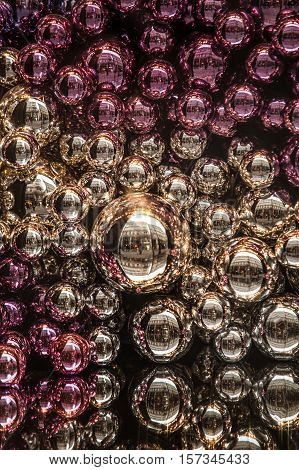 Filled frame composition with colorful Christmas balls of pink silver and purple color. Selective focus vertical image
