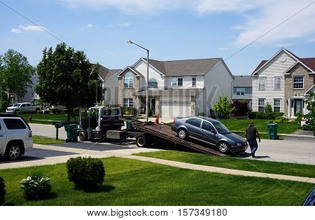 JOLIET, ILLINOIS / UNITED STATES - MAY 24, 2016: A tow truck prepares to remove a disabled vehicle from the Wesmere Country Club subdivision of Joliet.