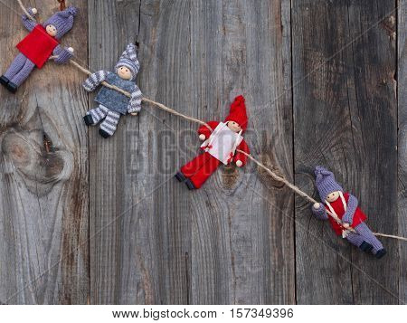 Rag dolls hanging on a rope gray wooden background