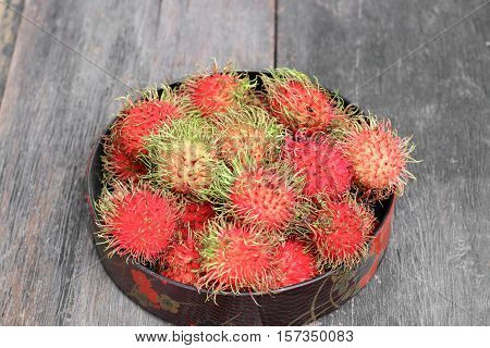 rambutan sweet fruit fresh in plate on wood background :Select focus with shallow depth of field.