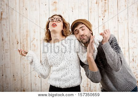 Young handsome man unnerve his girlfriend holding phone over wooden background.