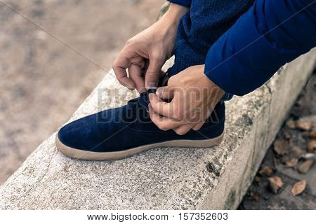 young man tying shoelaces on blue sneakers