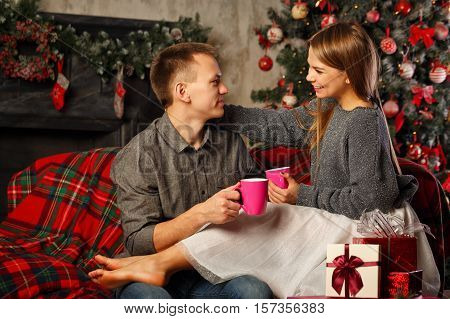 Loving couple and Christmas. The guy and the girl sit on a couch and drinking a hot Christmas drink tea. Girl barefoot. In the background a beautiful Christmas tree.