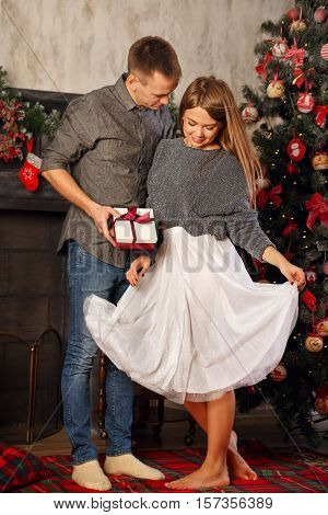 Loving couple and Christmas. He gives a girl a Christmas gift. In the background a beautiful Christmas tree.