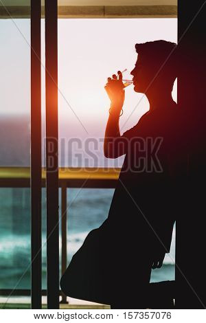 Silhouette of handsome brazilian guy drinking water from transparent glass on the balcony near window on sunset teal ocean and horizon outside Rio de Janeiro Brazil