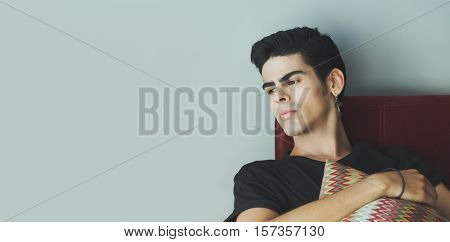 Thoughtful young handsome brazilian guy with brown eyes black t-shirt cross earring is seating on dark red sofa with gray wall behind and looking down holding motley pillow in his hands