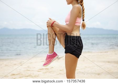 Cropped Shot Of Blonde Caucasian Girl With Beautiful Fit Body Doing Stretching Exercises Before Jogg