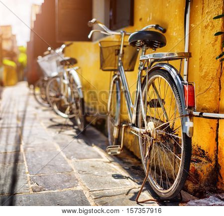 Bicycles Parked Near Yellow Wall On Sunny Street In Summer