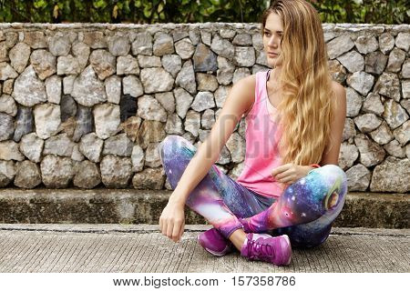 Outdoor Portrait Of Beautiful Caucasian Woman Jogger With Long Blonde Hair Wearing Pink Sports Top A